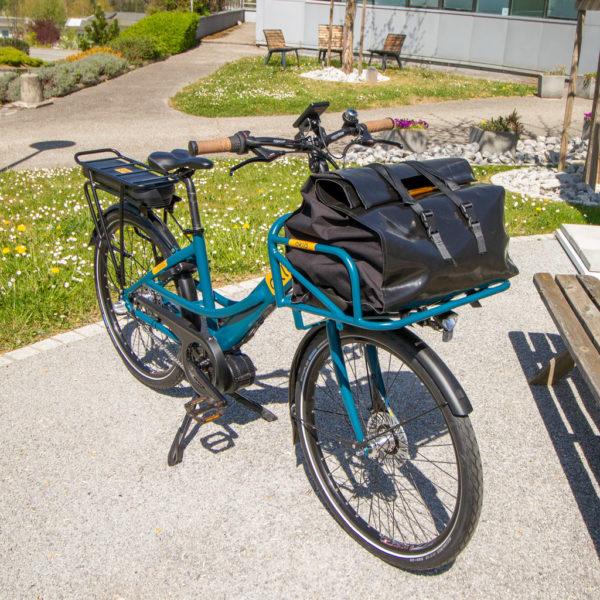 Vélo Postal 500Wh avec sac dans porte-bagages avant